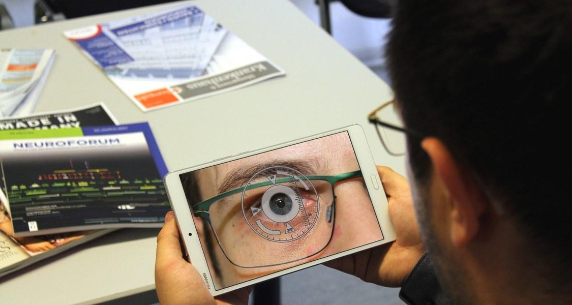 Ein Proband führt im Wartezimmer eine Messung der Augenbewegungen mittels Tablet-Computer durch